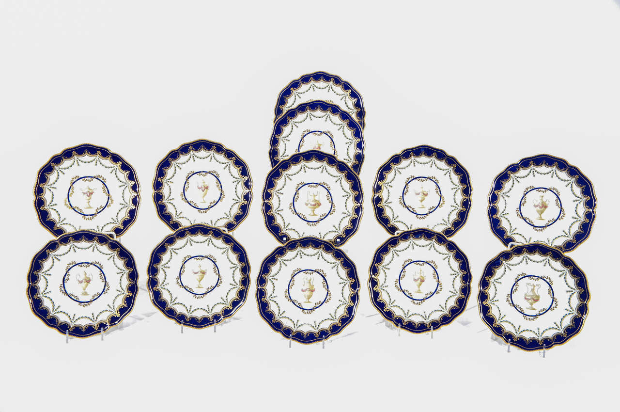 An unusual set of 12 Royal Crown Derby dessert plates featuring an elegant and restrained central subject of subtly different urns with floral decoration encircled with swags of golden leaves. The shaped rims are bordered with cobalt blue with
