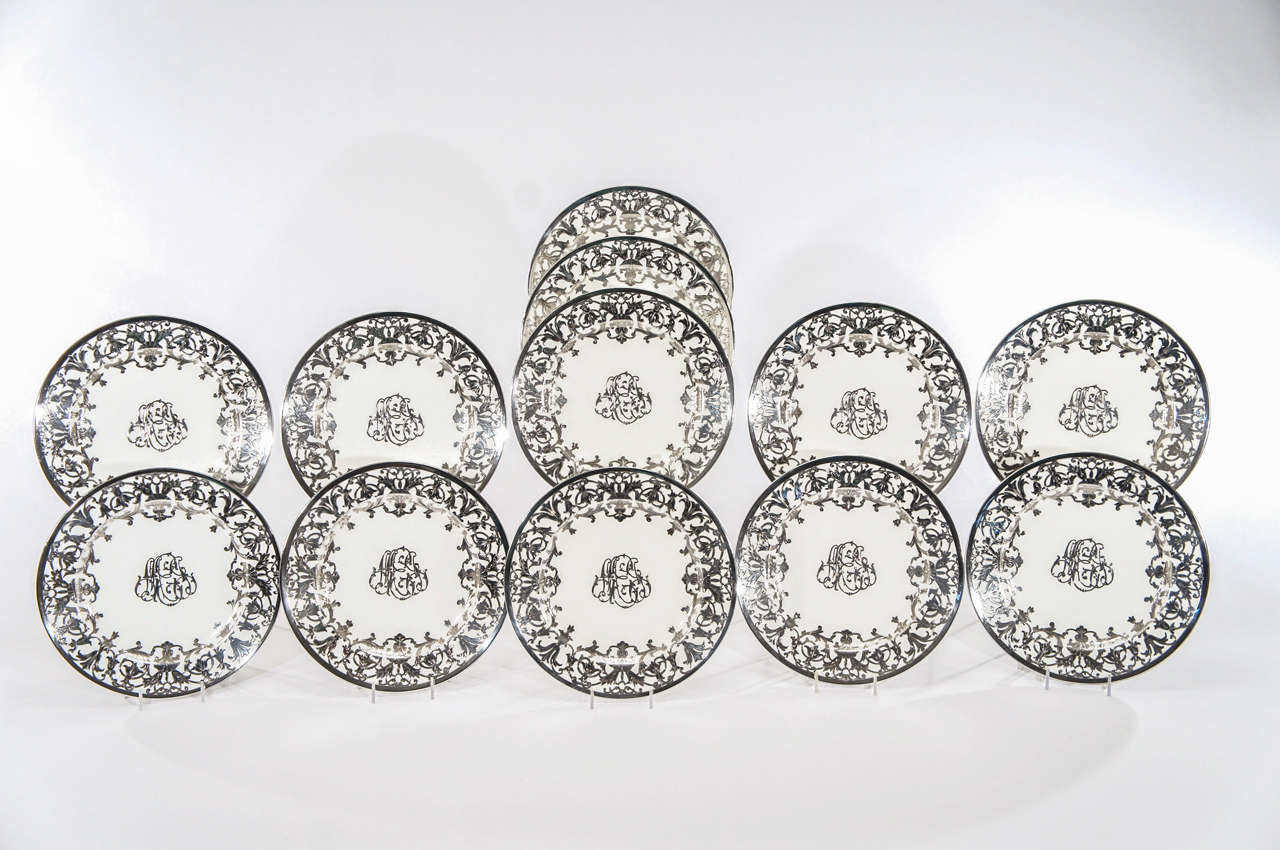 This set of 12 Minton service plates is a rare example of Minton's sterling silver overlay. Most silver overlay was made by other porcelain manufacturers and these were surely a custom order. The thick, heavy and profuse silver work, extremely