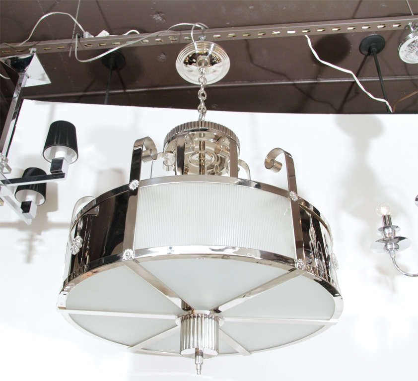 Outstanding Art Deco chandelier with nickeled bronze.  Features a fluted cylindrical drop-finial, textured curved glass panels, and two tiers of strapwork accents terminating in scrolling volutes at top.  Formerly hung in The Grand Foyer of San