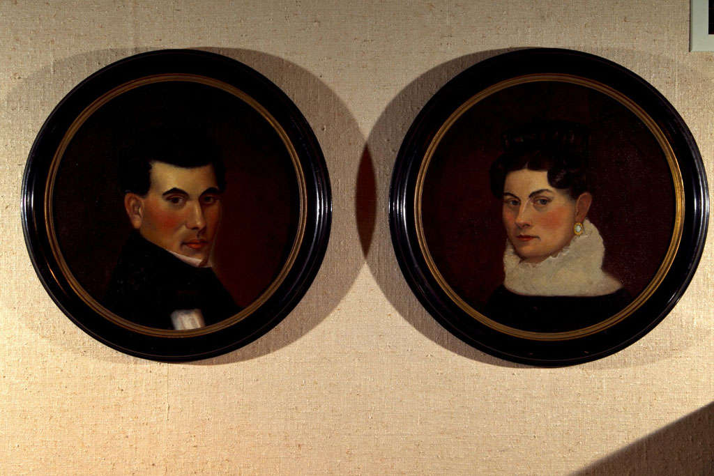 This stern couple peers out at us through unique porthole frames from the period. Painted on canvas, they have been re-stretched onto wood backing and retrofitted to these frames, looking none the worse for the wear--though perhaps it was the move