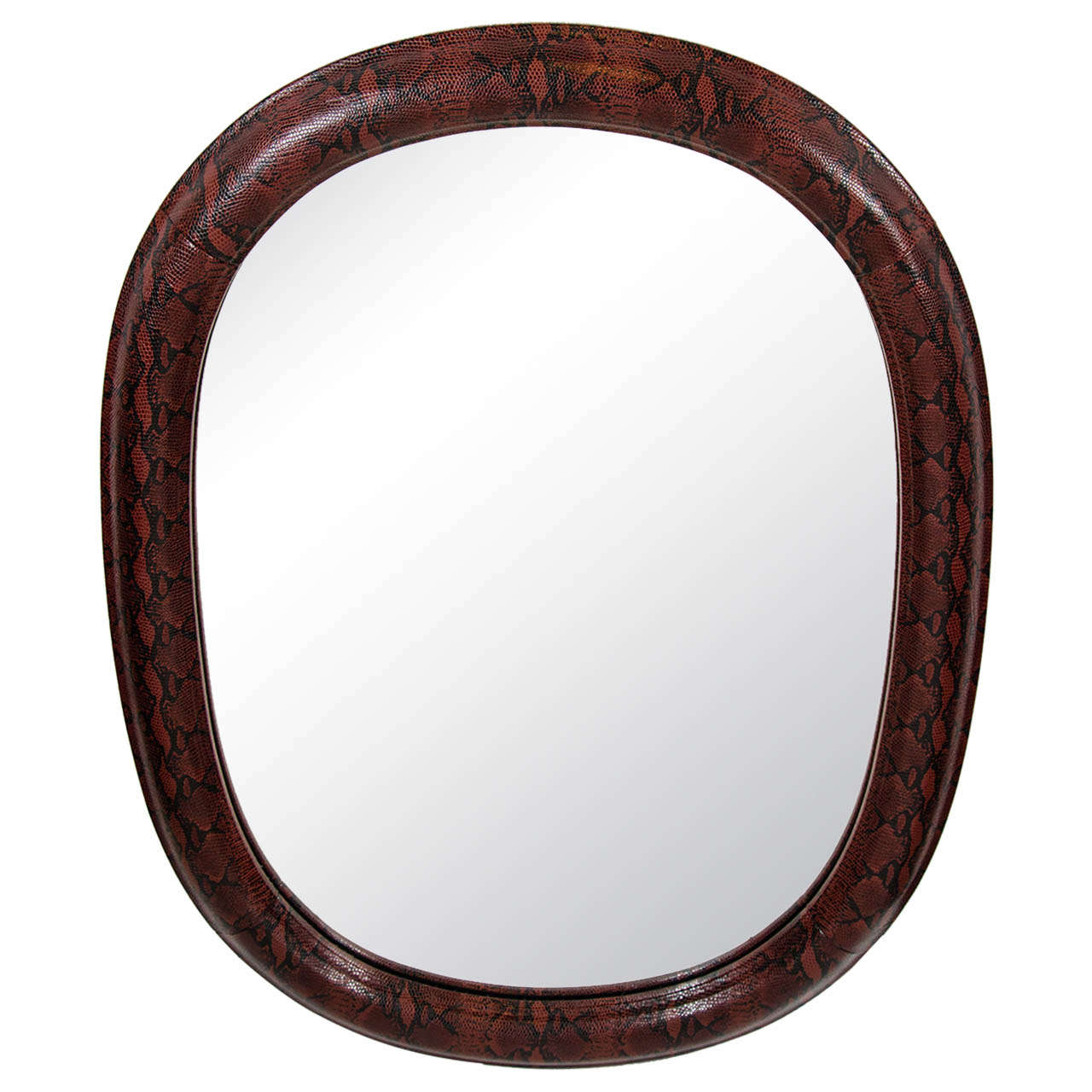 Stunning mid-century modern rounded mirror with slight oval form. Wrapped in red and black snakeskin print embossed leather. Leather over hand-carved wood with half round molded frame. In the style of Karl Springer.
