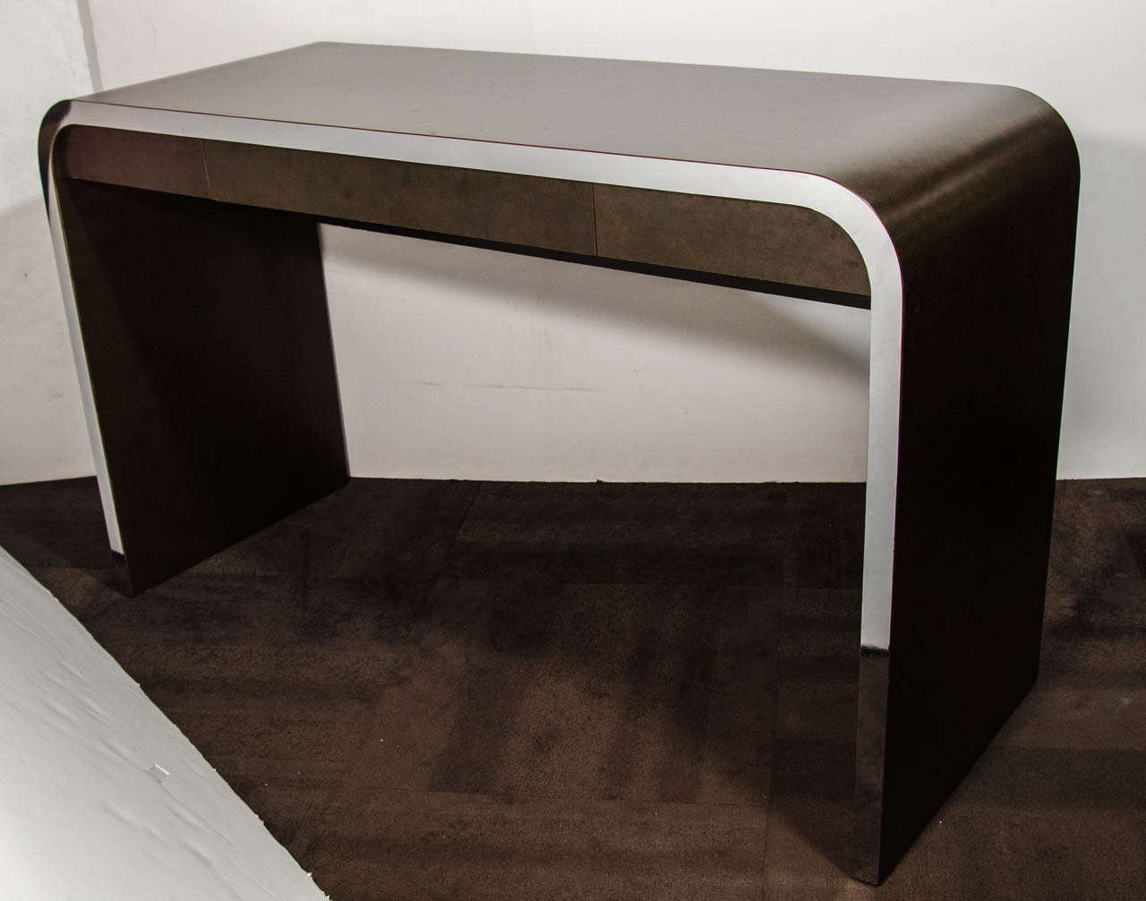 Modernist writing table and console table in dark burled wood laminate with stylized chrome banded details. The table has a waterfall design with streamline curved edges, and is conveniently fitted with a narrow center drawer. The console is