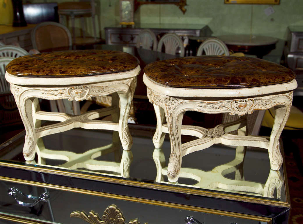 Pair of French Louis XV style low footstools, the white distress-painted frame with brown worn leather cushion over a caned top.