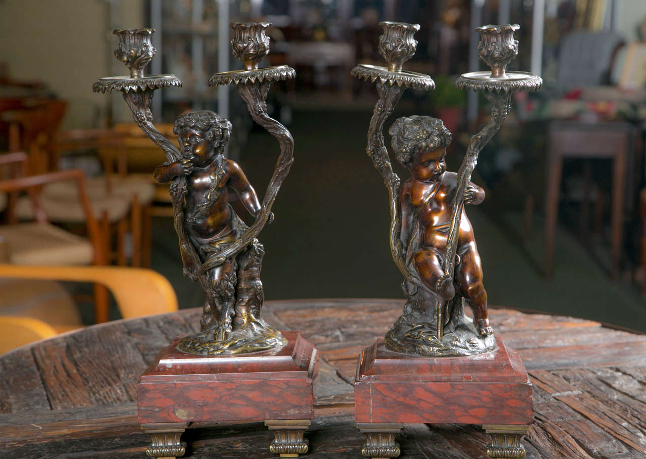 A pair of French Rococo style candelabra after Claudion.  Bronze set upon rouge marble base.