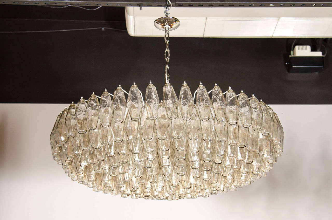 This exquisite Murano glass chandelier was realized in Murano, Italy, the island off the coast of Venice renowned for centuries for its superlative glass production. It features numerous hand blown Murano glass polyhedral shades in transparent glass
