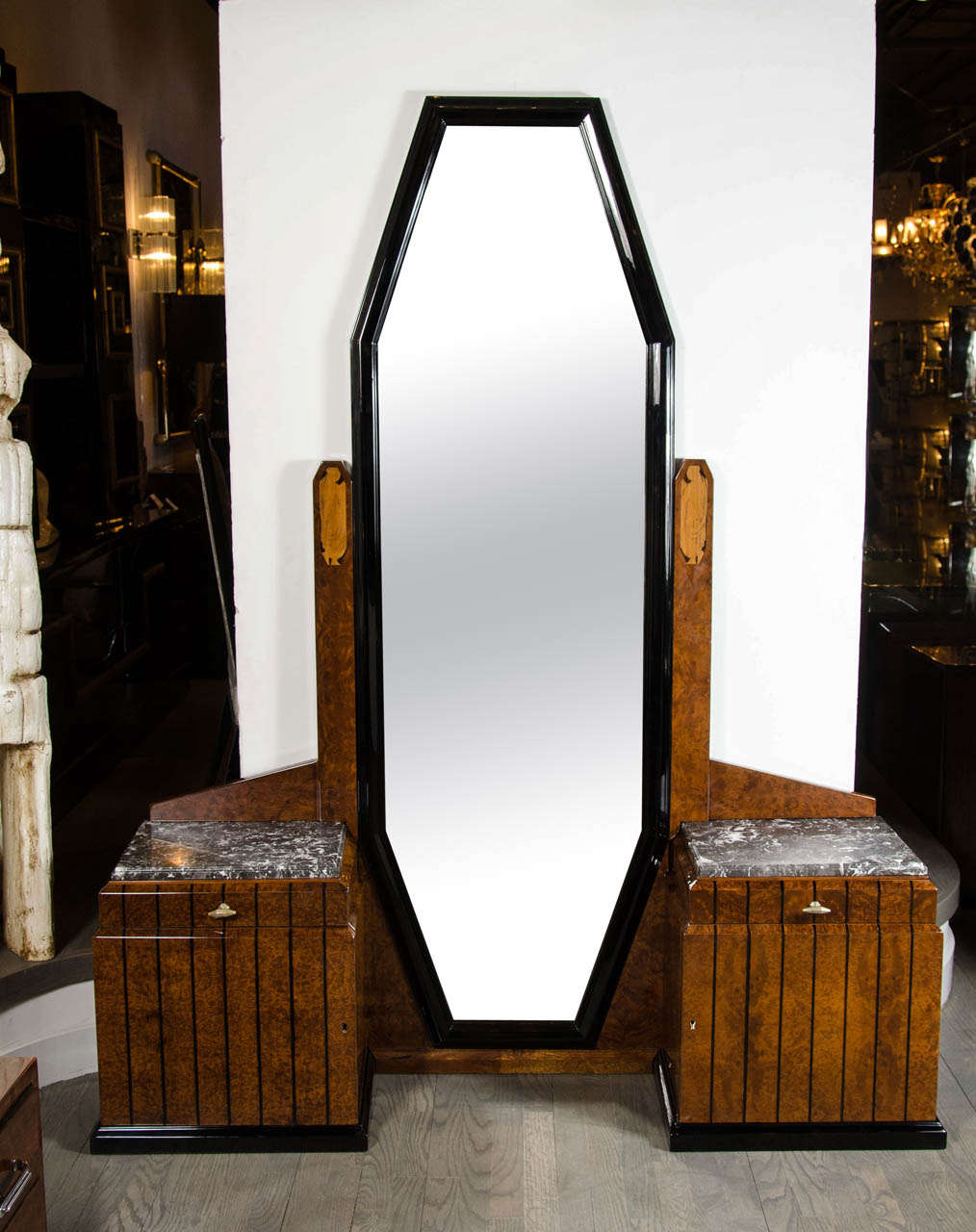 This elegant Art Deco floor-standing vanity or dressing mirror in book-matched burled elm features strong skyscraper Art Deco cubist geometric details, a full length octagonal mirror flanked by two exotic marble-top cabinets, each fitted with a