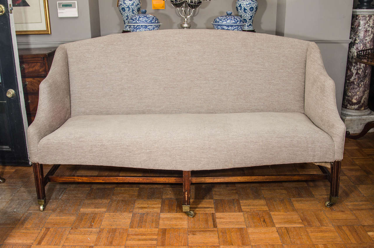 Hepplewhite sofa. On six tapered legs with spade feet, connected by stretchers and with original casters.