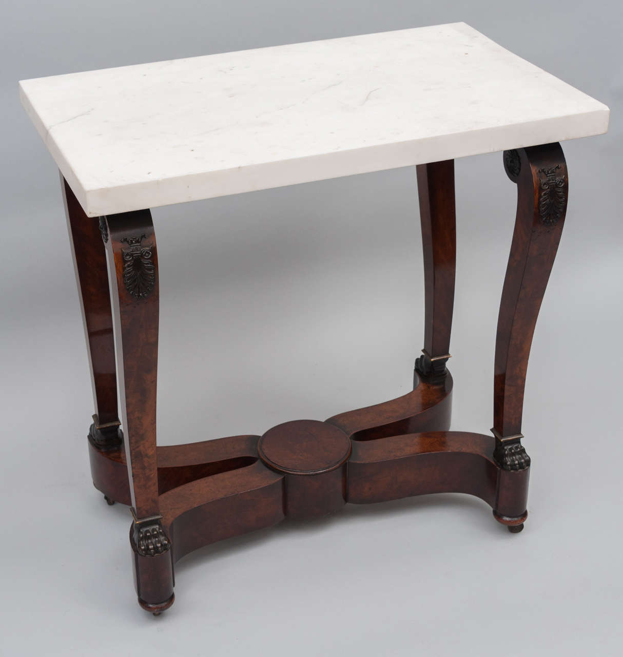 A good quality early 19th century French empire centre table of figured mahogany. The white statuary deep marble top set on scroll supports mounted with bronze anthemions and rosettes terminating in bronze lion paw feet, onto on a bold swept x-frame