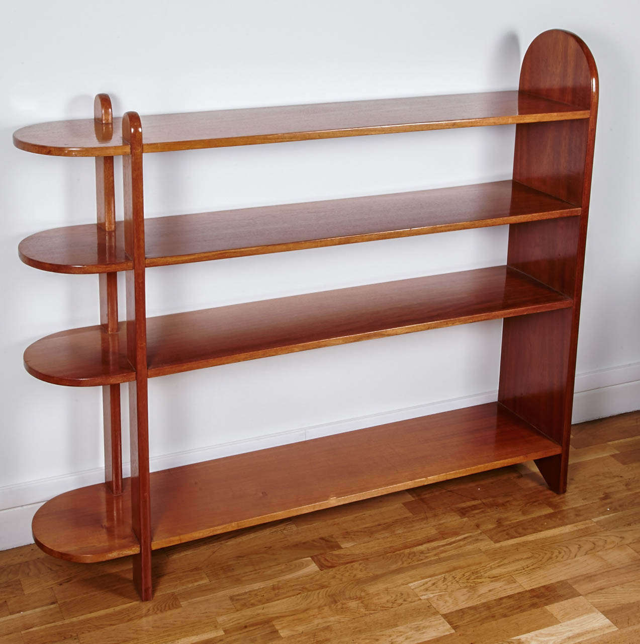 Light mahogany shelves bookcase with four shelves. One side of each shelf has an arc of a circle shape. 1932 iconic model from Eugène Printz.