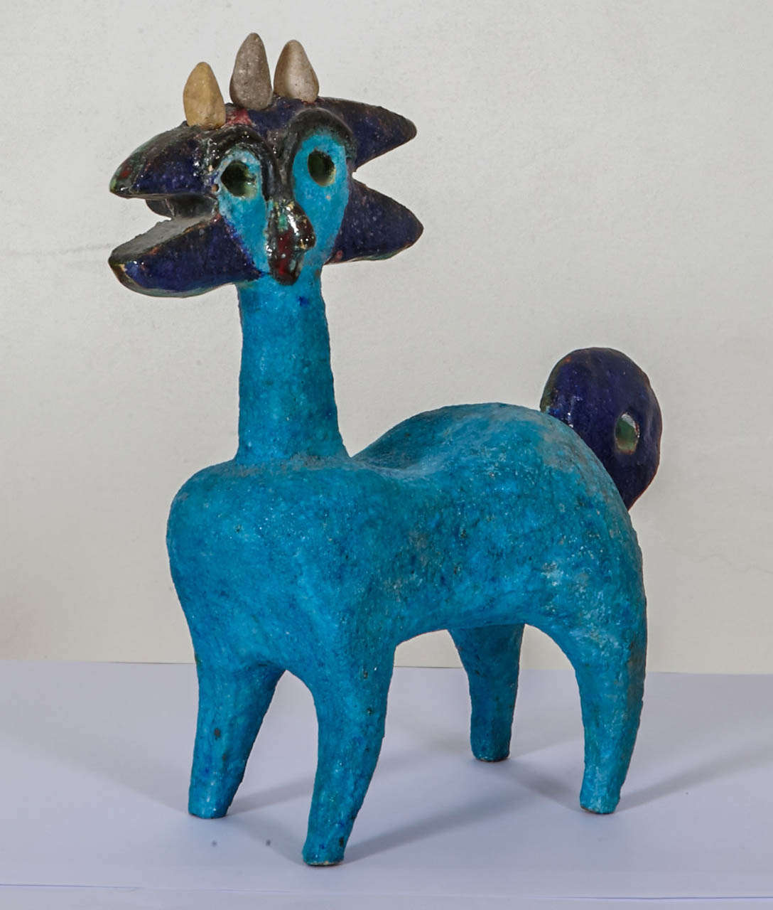 """Double faced blue enameled earthenware """"Fabulous zoomorphic idol, circa 1960-1965, by Guidette Carbonell (1910-2008) With green, red, black colors too. Stone horns. Unique piece, monogrammed. Re´f : F.Bodet, K.Lacquemant, Guidette Carbonell,"""