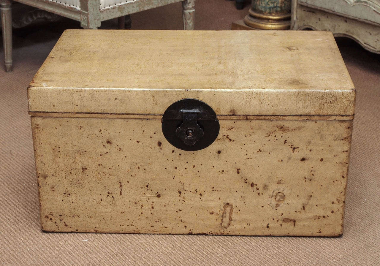 Chinese parchment trunk with red lacquered interior.