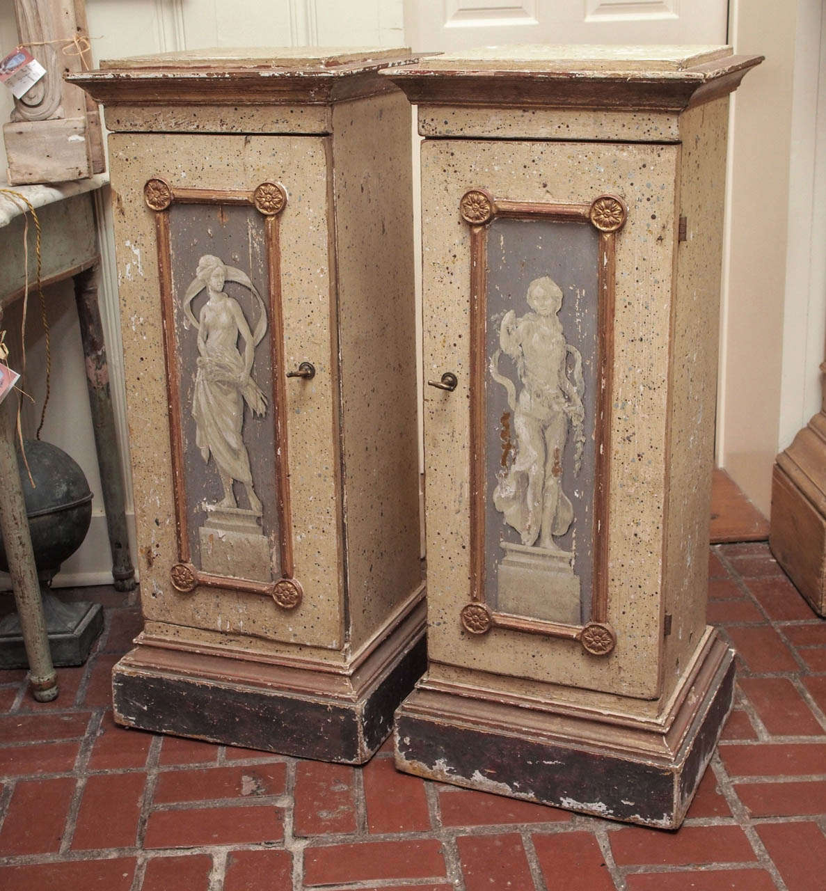 A pair of 19th century Italian painted plinths with faux bas relief motifs and giltwood accents. They are actually cabinets with one interior shelf. Original hardware and keys.