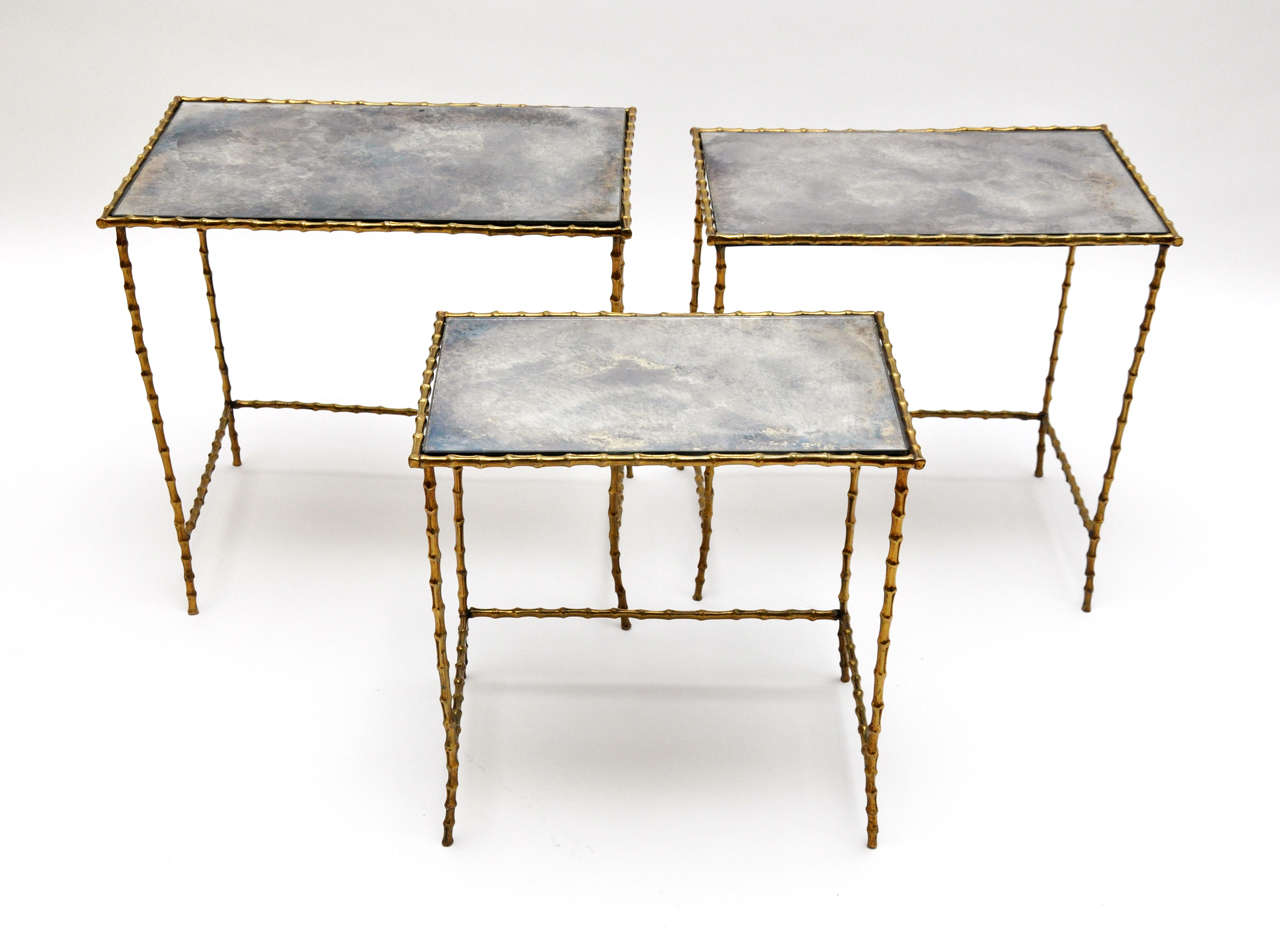A chic set of three brass bamboo and antiqued glass top for Glass top nesting tables