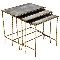 A Chic Set of Three Brass Bamboo and Antiqued Glass Top Nesting Tables