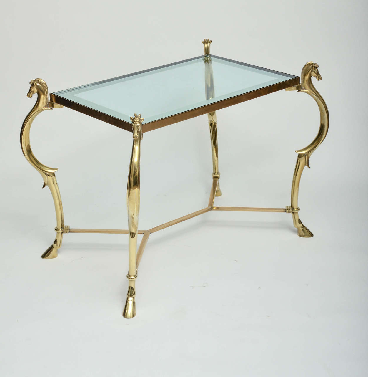 Pair of curvilinear brass side tables with horse head finials and mirror trim glass tops.