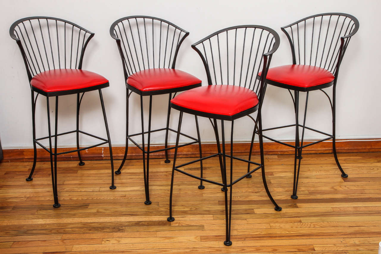 Wrought iron bar stools with original red vinyl upholstery. Signed with manufacturer's sticker to underside of frame.