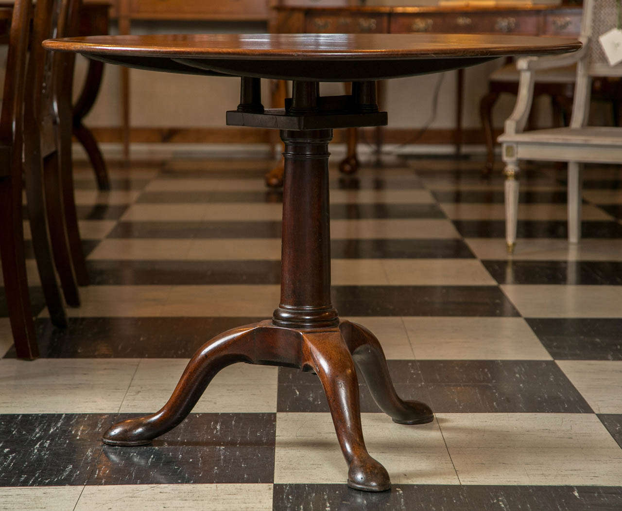 While there is nothing extraordinary about this mahogany tilt-top table no fancy, carved edge or claw and ball feet there is nothing particularly ordinary, either. The top is just the right thickness for the diameter and the pedestal is weighted