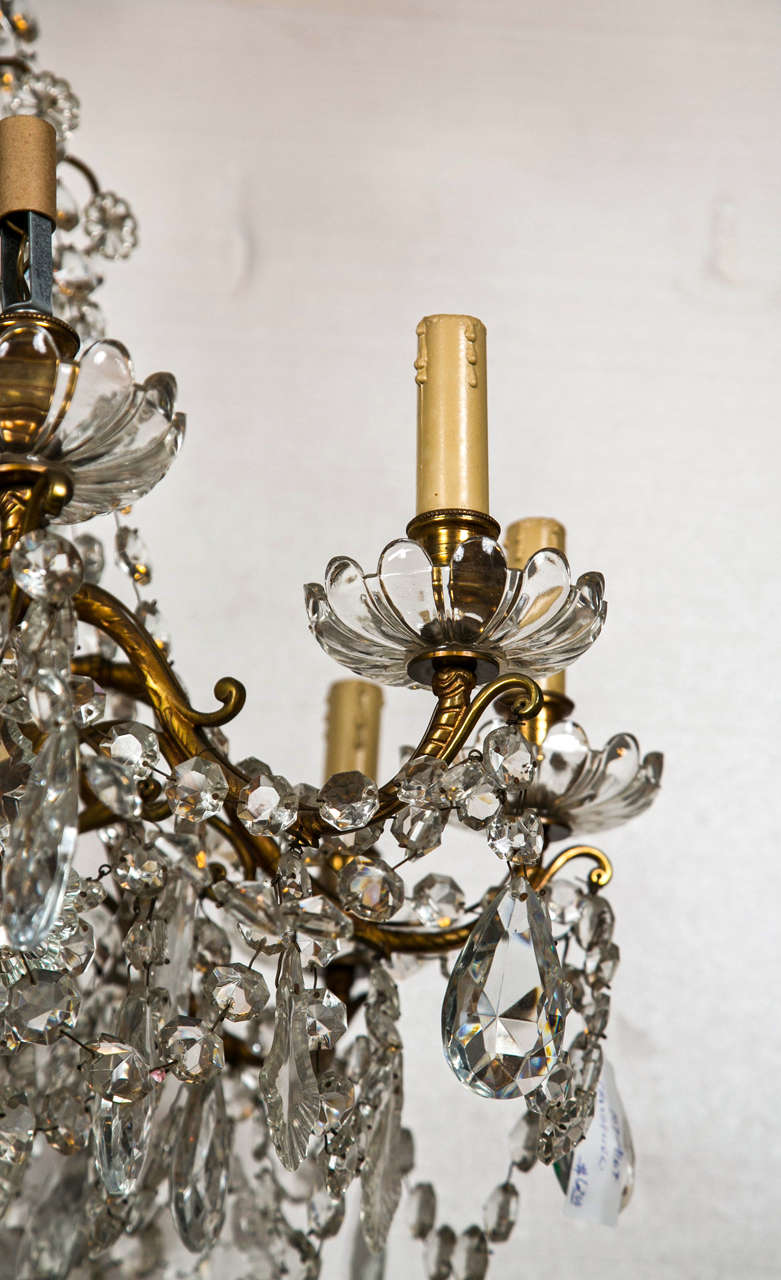 A fine cut glass Georgian Style Crystal central column and bronze chandelier. This twelve light candelabra style chandelier possiblly waterford or baccarat crystal. The crystal bobeshes under finely cast bronze lights. The overall design very