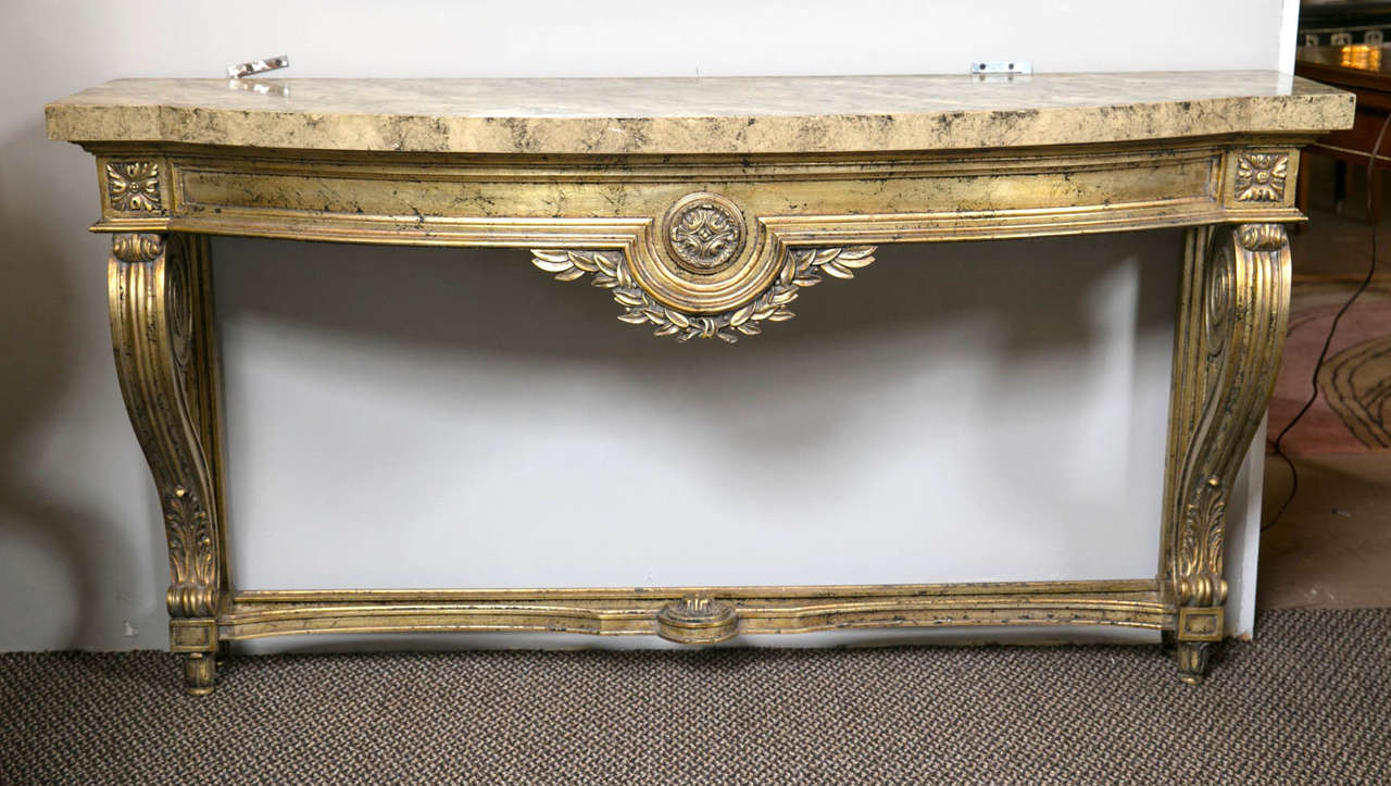 Faux marble-top Louis XV style console table attributed to Maison Jansen. This finely distressed silver goldish leaf console is very decorative. The wonderfully painted faux marble wall mount sits atop a case with a central leaf and vine decoration