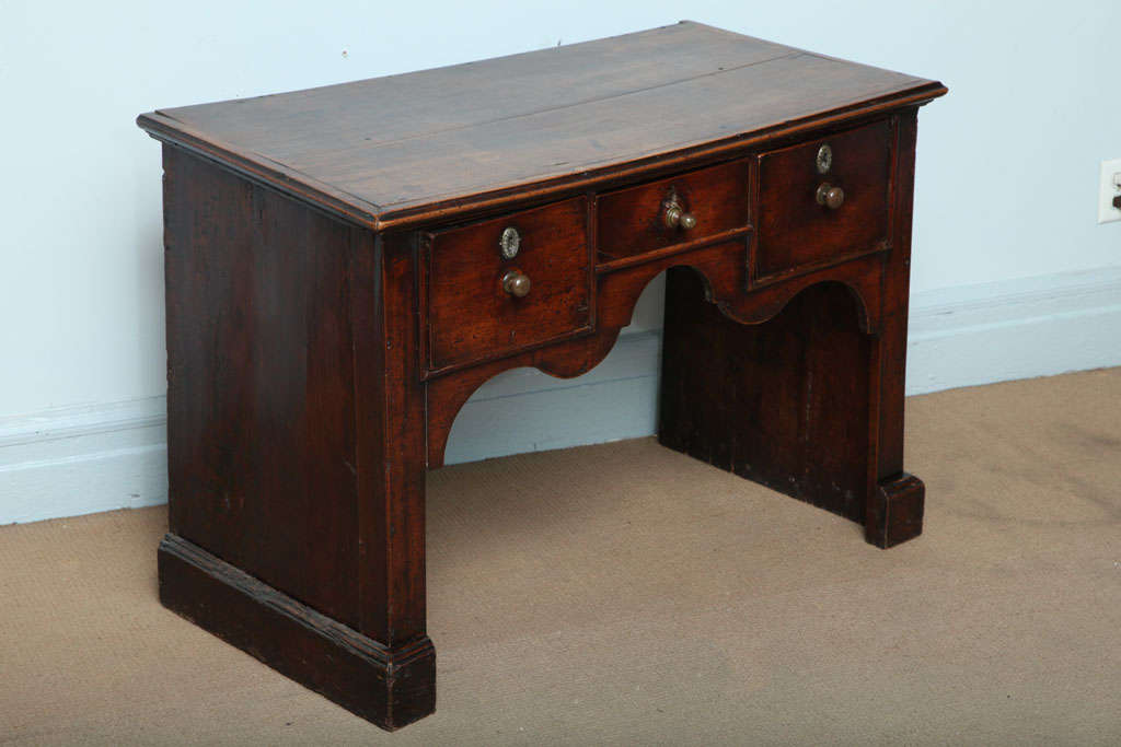An unusual English 18th century fruitwood lowboy or dressing table having richly molded top over three drawers and solid sides, finished with molded feet.  Good color and rich patina.  Overall of very architectural form.  circa 1760.