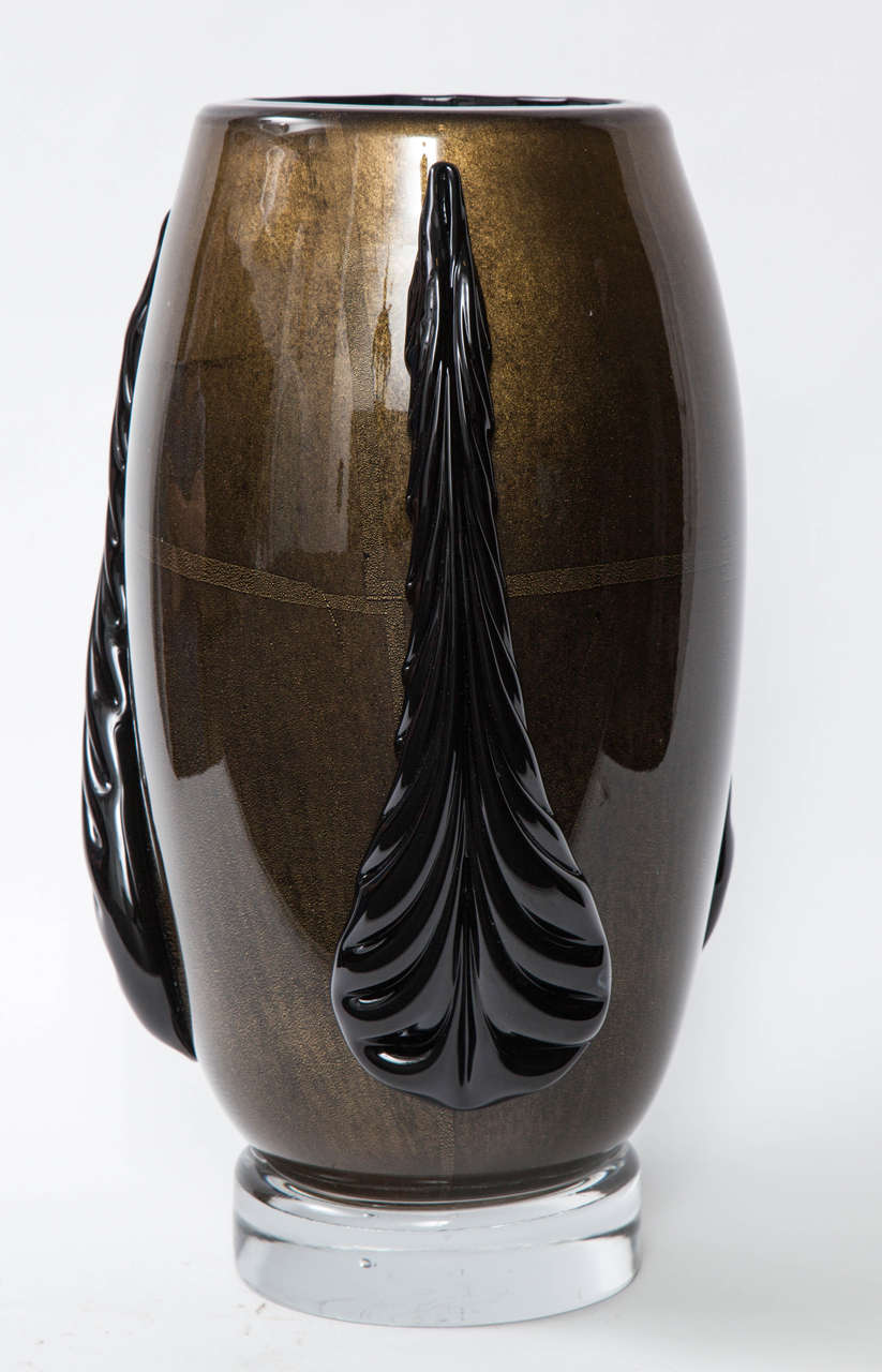 Art Deco inspired vase made of black Murano glass with 22-karat gold dust outer layer and applied black glass stylized leaf forms, sitting on thick clear glass bases. Exquisite craftsmanship. Signed on bottom.   Currently a pair is available.