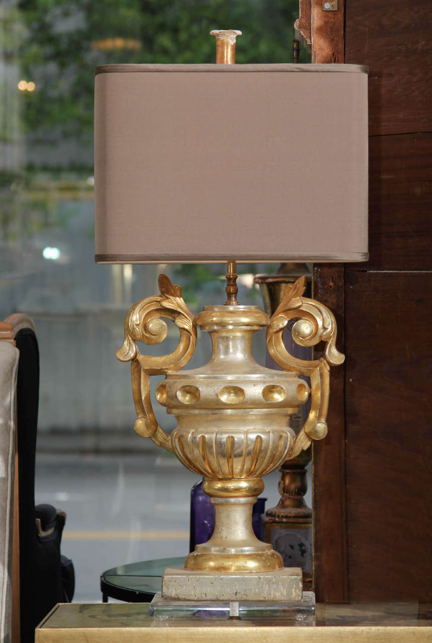 Pair of custom lamps of gilded carved wood fragments from France on plexiglass bases with oval silk shades.