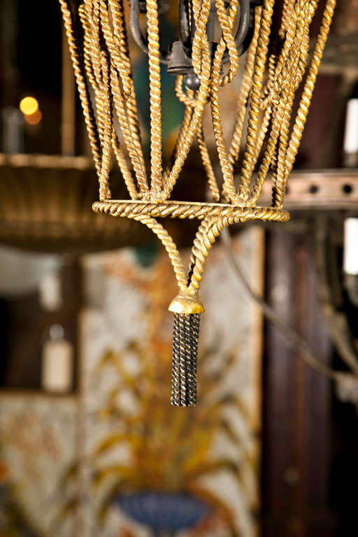 Gilt metal rope and tassel pendant light with four bulbs.