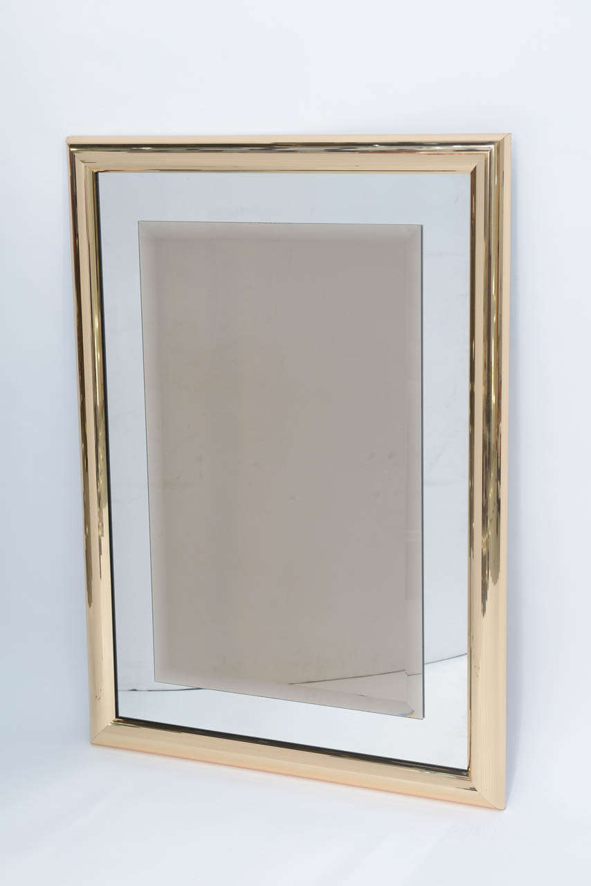 """Sleek disco era mirror with mirror ball-like micro faceted frame of brass. The mirror features a mirrored glass with a floating bevelled bronze mirror in the centre. Quite elegant and glamorous.   Measures: 39"""" x 28"""" x 2"""" deep."""
