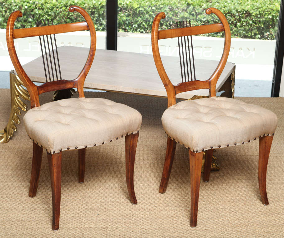 Beautifully restored, this pair of side chairs are great in scale and very comfortable. They feature a harp like back and a delicate tufted linen seat.