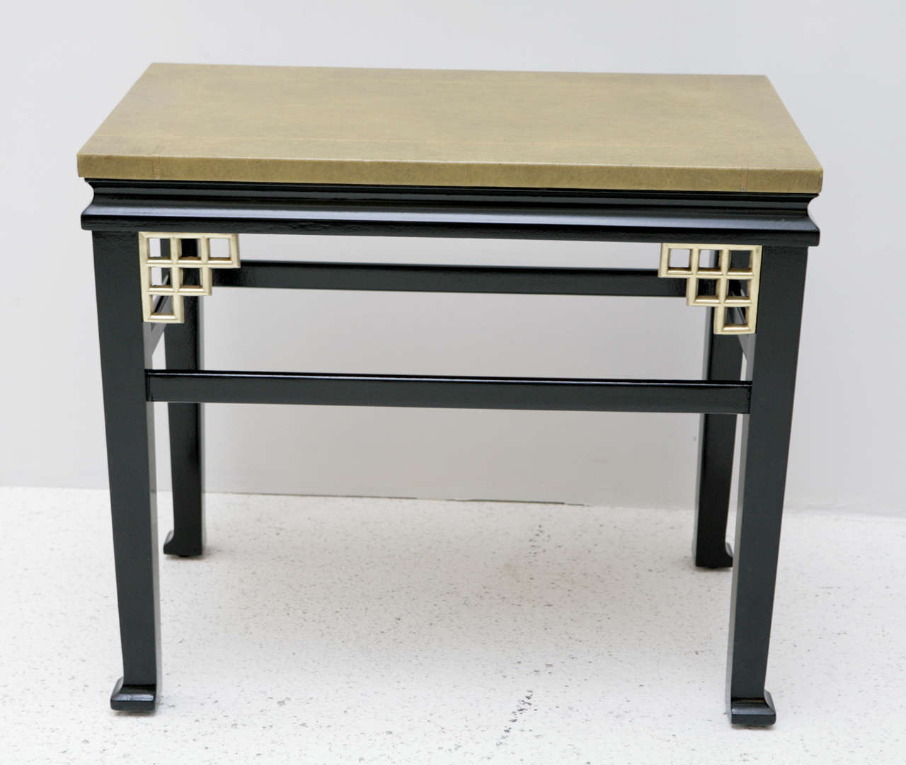 A pair of custom side tables with gold greek key embossed leather tops and satin finished black bases accented with brass fretwork details in the corners. These tables are most certainly custom work based on the construction and quality, it is