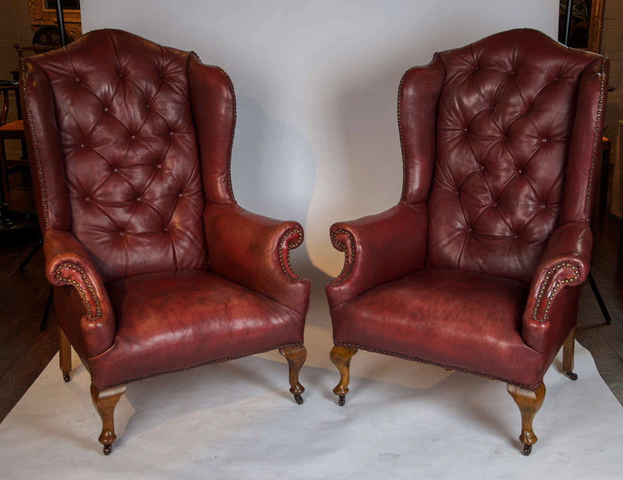 A Good Pair Of Early 20th Century Wing Back Chairs With Original Read  Leather And Buttoned