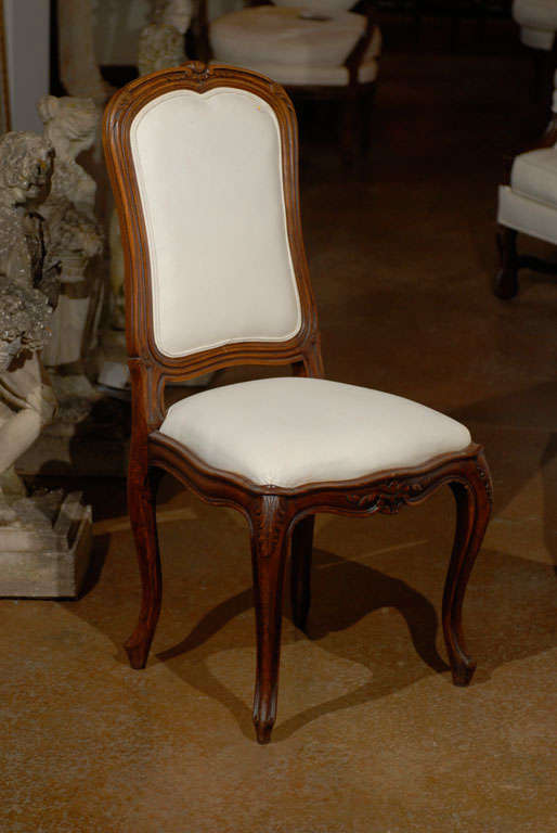 A set of six French Louis XV style walnut dining room side chairs from the 19th century, with scalloped apron, cabriole legs and new upholstery. Each of this set of French Louis XV style chairs features a delicately carved, slightly slanted back,