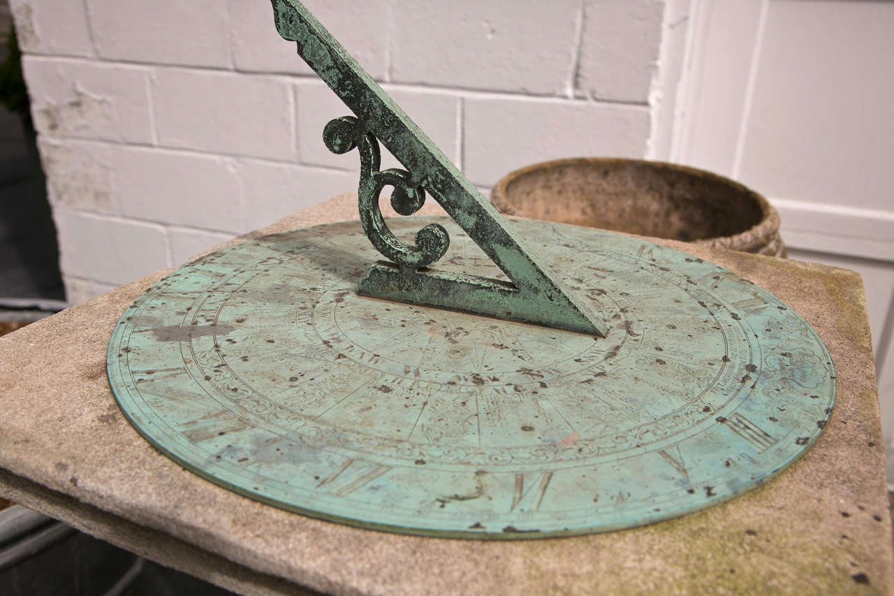 Barker & Sons London, bronze and limestone sundial having an unusually large dial and gnomon.