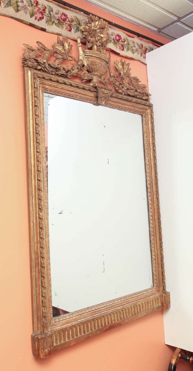 A large Louis XVI giltwood console mirror with urn and foliate swagged crest, ribbon carved molding and fluted frieze.