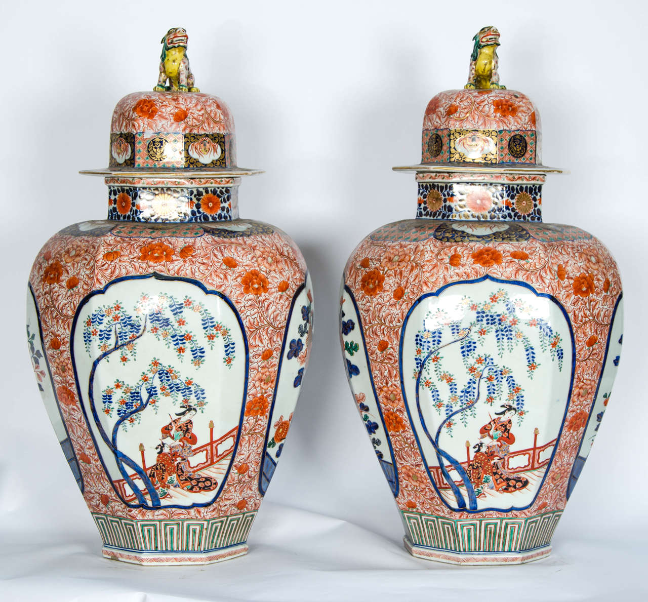 A large and impressive pair of 19th century Japanese Imari lidded vases, having dogs of faux to the lids, hand-painted floral panels and surrounds of wisteria and chrysanthemums.