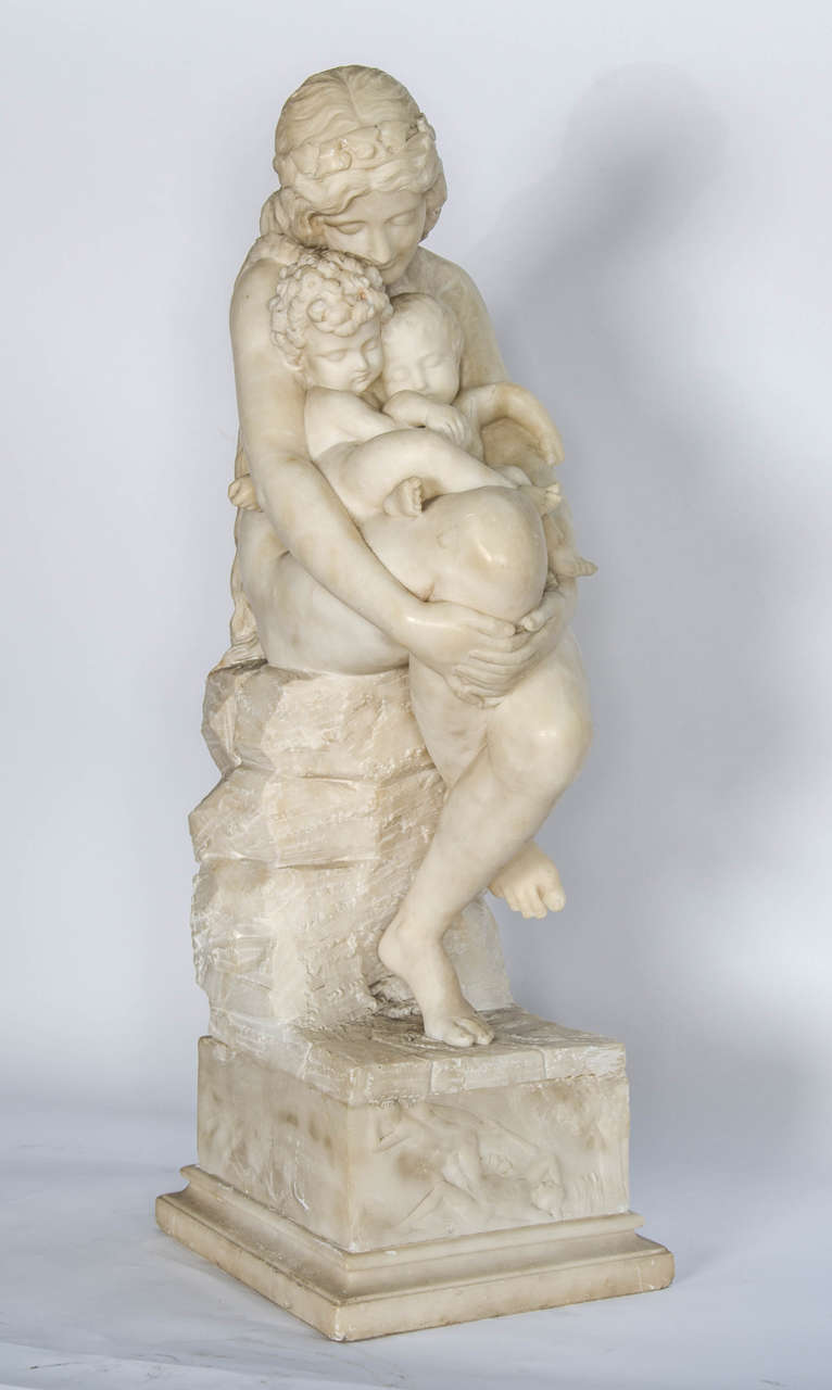 An enchanting Italian, 19th century Alabaster study of a mother and her two children, seated on a rock.