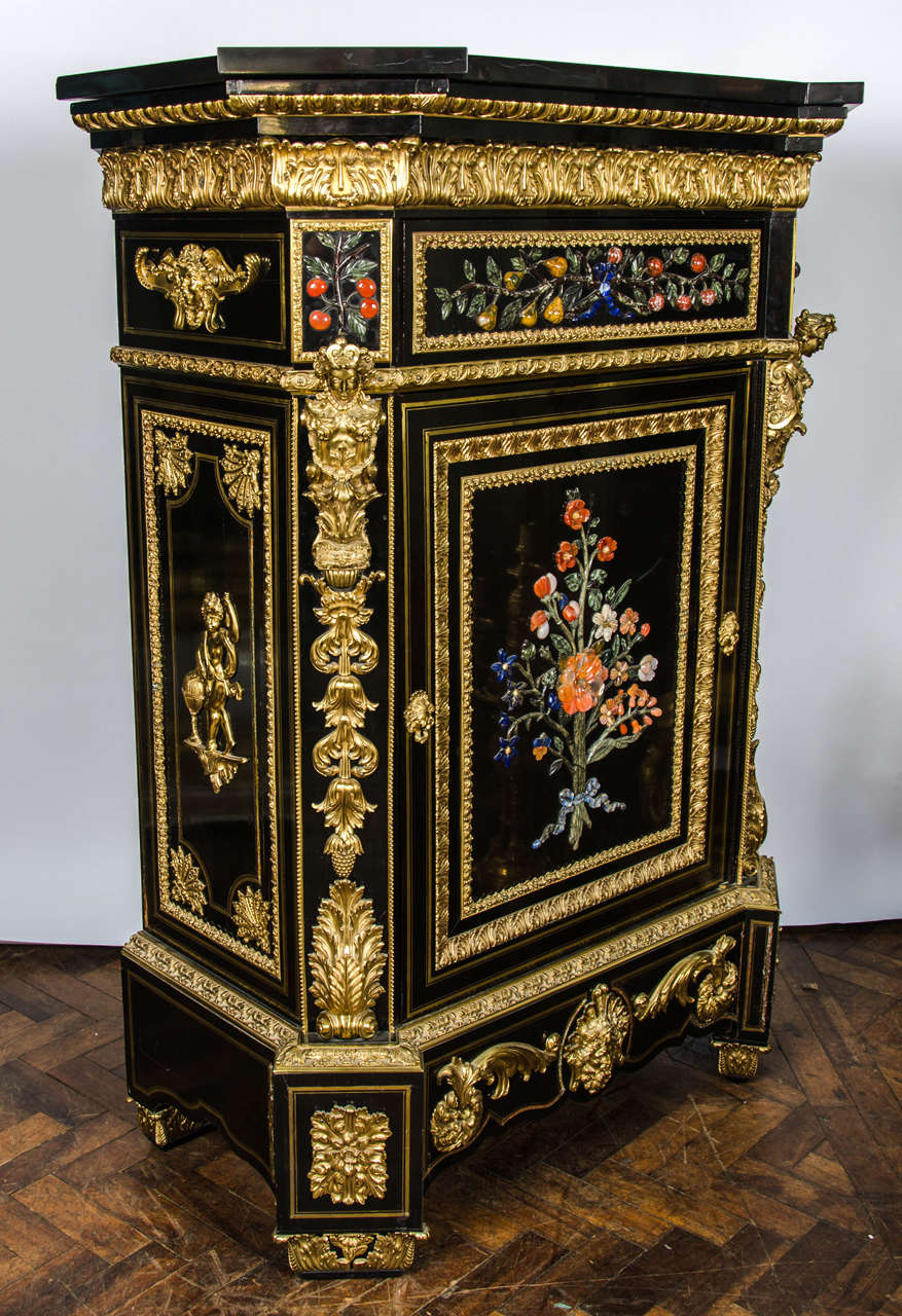 A monumental pair antique Pietra Dura inlaid ebony veneered pier cabinets. Have the original black marble tops, wonderful gilded ormolu mounts and inlaid foliate decoration to the doors.
