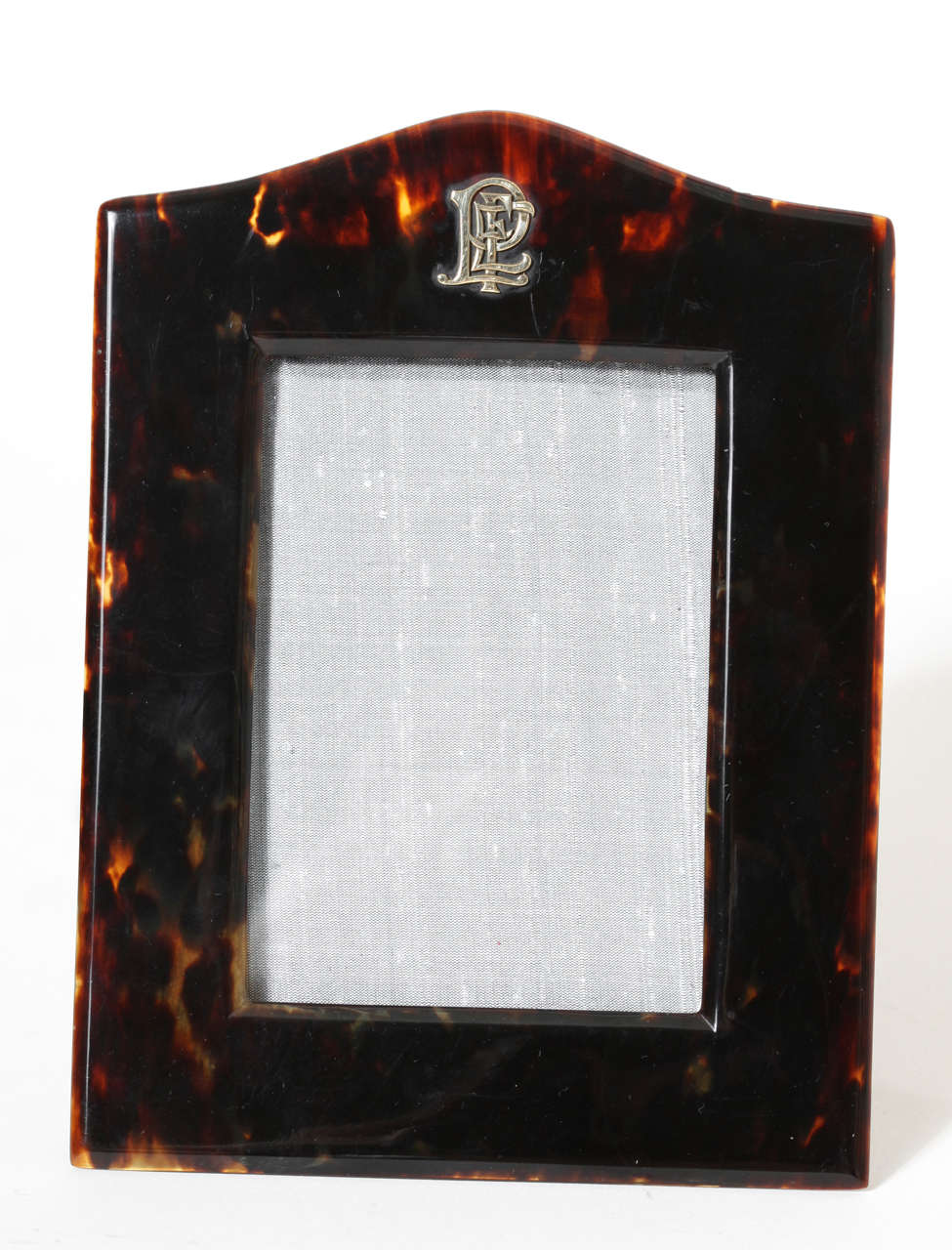 Rectangular photograph frame with arched top and fancy gold FEP monogram. Original leather back and stand. Stamped: ASPREY LONDON on back.