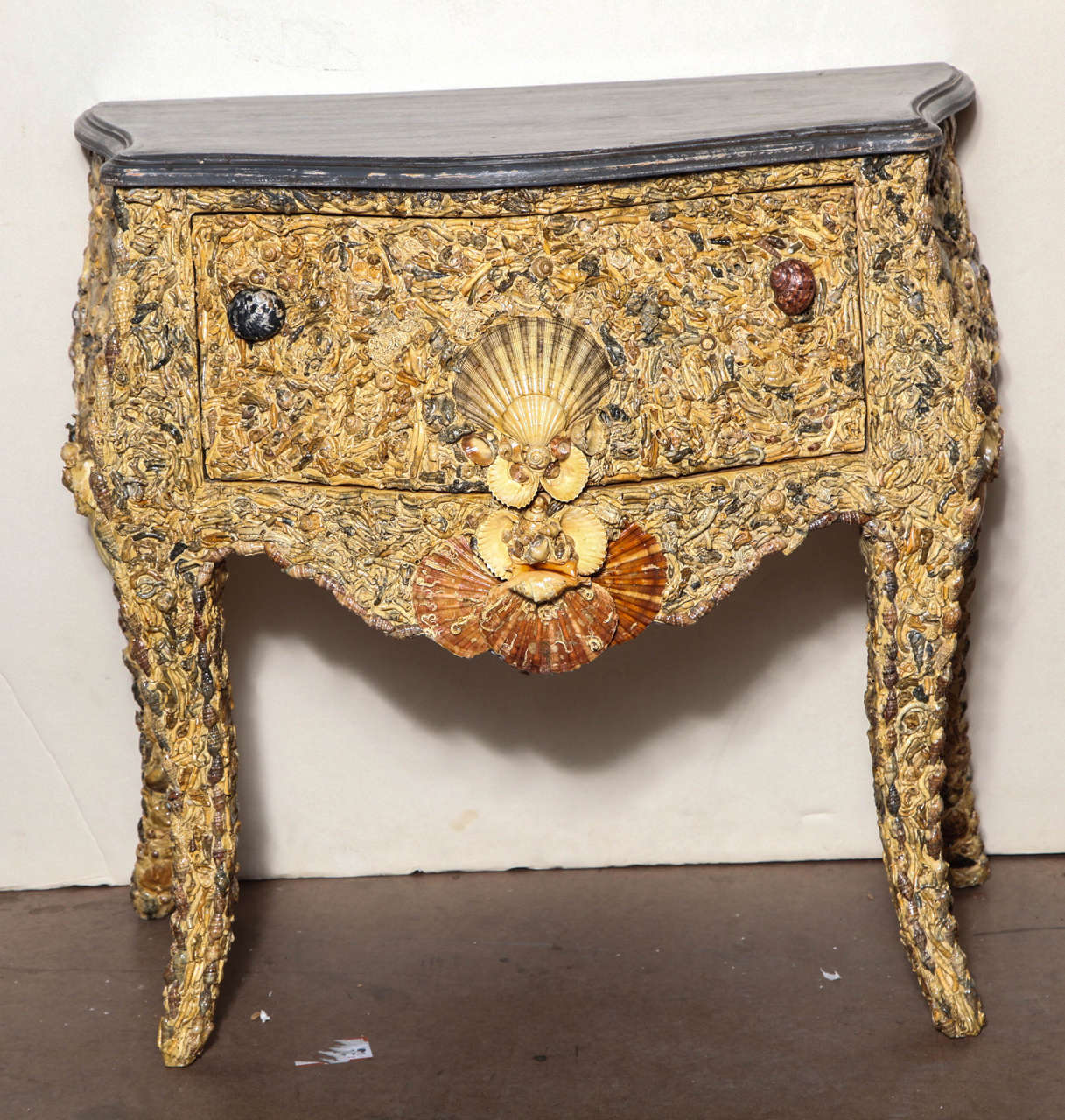 "19th century Italian grotto shell commode with faux grey marble painted serpentine top over a drawer with shell pulls; on inward curving legs. Signed ""M. Ruggeri"" on back."