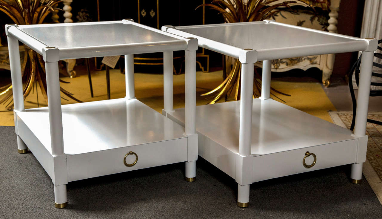 A pair of baker white lacquered end tables. Each having a bronze sabot foot leading to a single drawer and lower shelf area. The whole supported by circular columns terminating in bronze caps and an upper framed shelving area. The secondary wood of