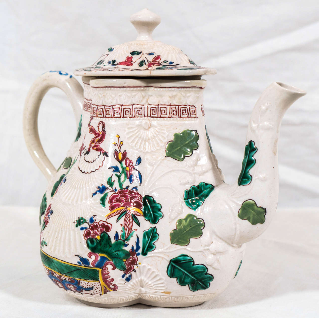 An antique salt-glazed teapot made in Staffordshire England in the mid-18th century. The salt-glazed teapot is beautifully painted. Made in the pectin shape with fine relief molded shell, acorn, and oak leaf decoration painted with translucent