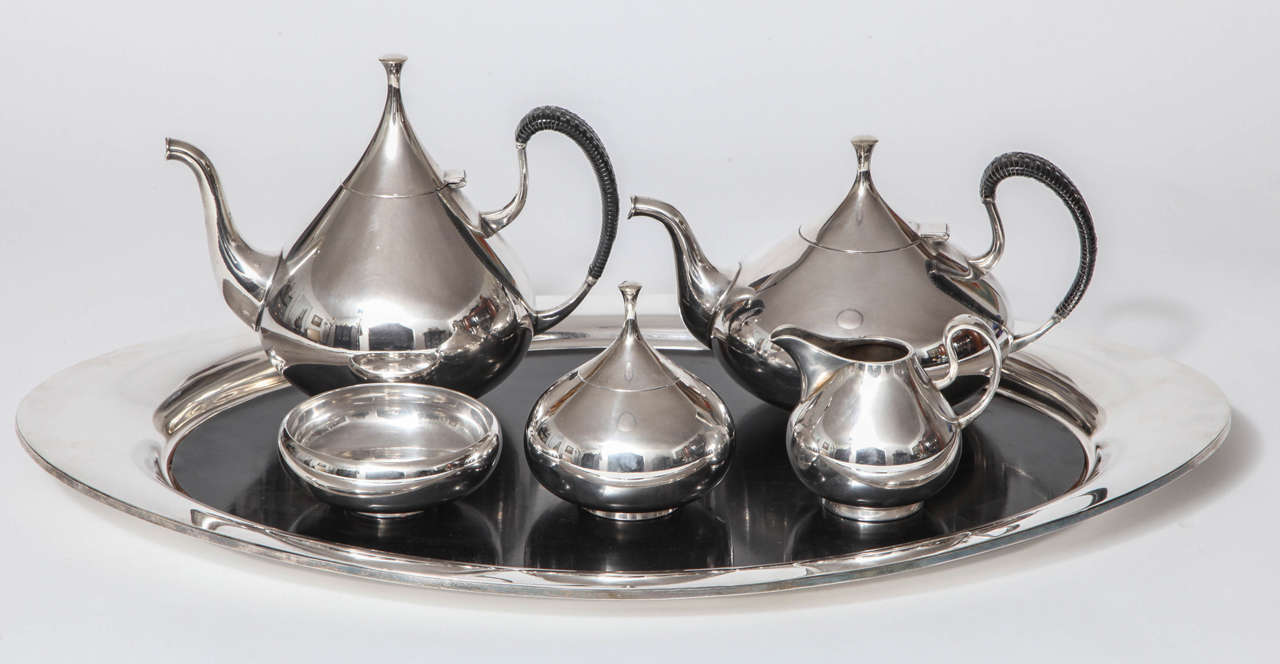 A complete tea and coffee service in silver plate with original laminate tray insert, designed by John Prip for Reed and Barton. Mint condition. The set is in the Dallas museum collection and is illustrated in Modernism in American Silver 20th