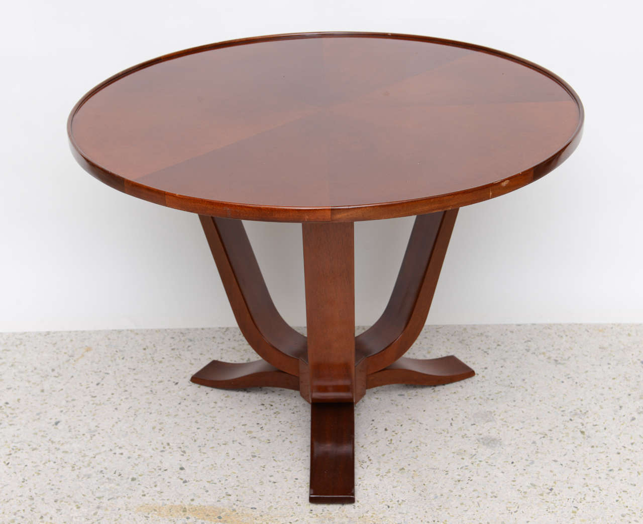 The radially veneered circular top above curved supports and legs joined by a central hexagonal support. Provenance Christie London.