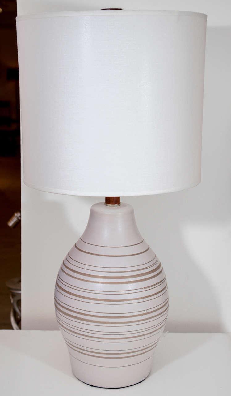 Fantastic bulbous form ceramic lamp in matte white glaze with horizontal tan stripes by Gordon Martz.