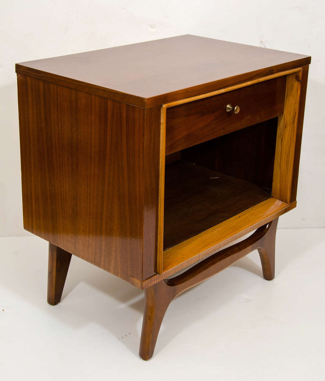 A pretty cube, crafted of walnut and birch and resting on a curved walnut frame. The cabinet has a single drawer, and large open compartment for books or periodicals. Perfect companion to any couch or bed; made to rest a beverage or book.