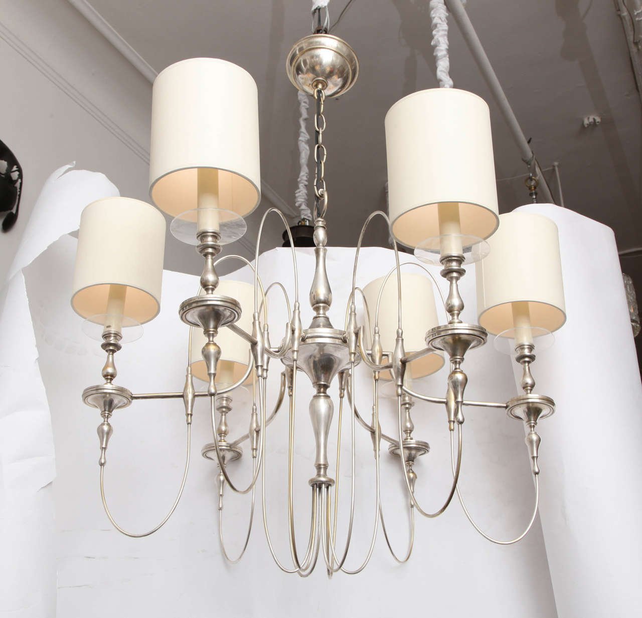 A 1940s art moderne candelabra chandelier, in silver-plate metal with six baluster motif arms, featuring elaborately scrolling stems. Shades not included