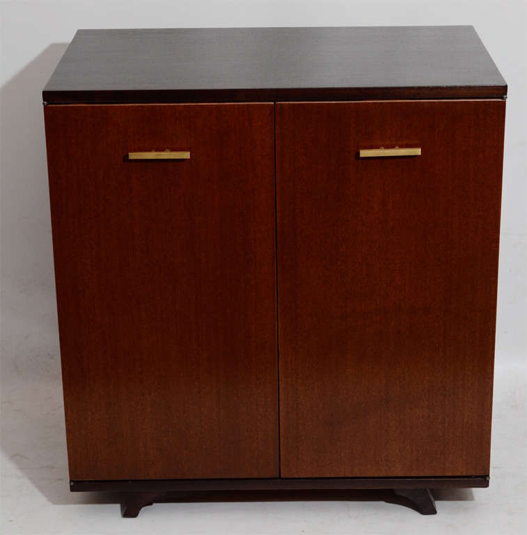 Handsome, modernist mahogany piece nicely stained in a two-toned exterior scheme. The drawer pulls are sleek and make a nice brass accent. Versatile for storage or as a media cabinet. Please contact for location. Offered by Las Venus by Kenneth