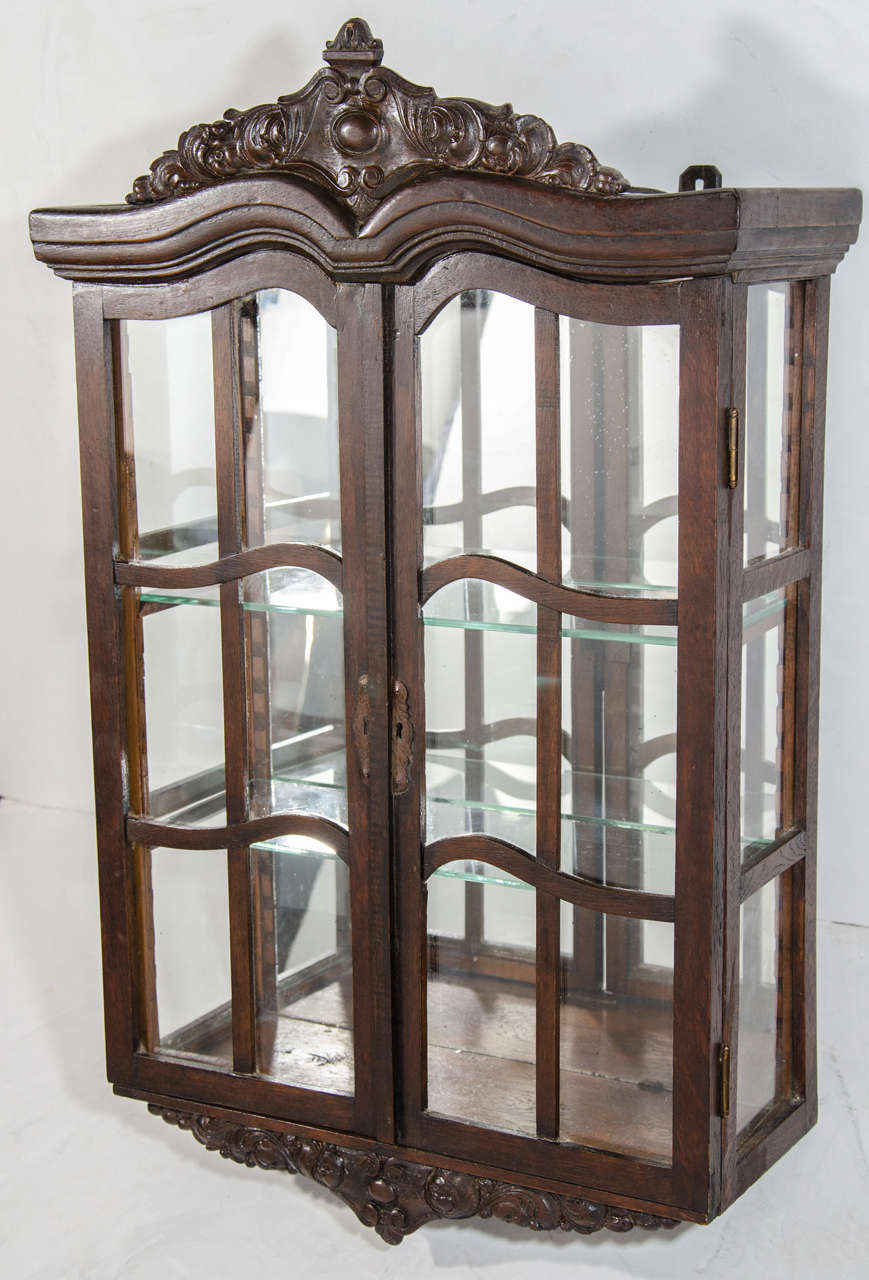Beautiful Antique Wall Mounted Curio Cabinet And Vitrine In Dark Wood With Hand Carved Crown
