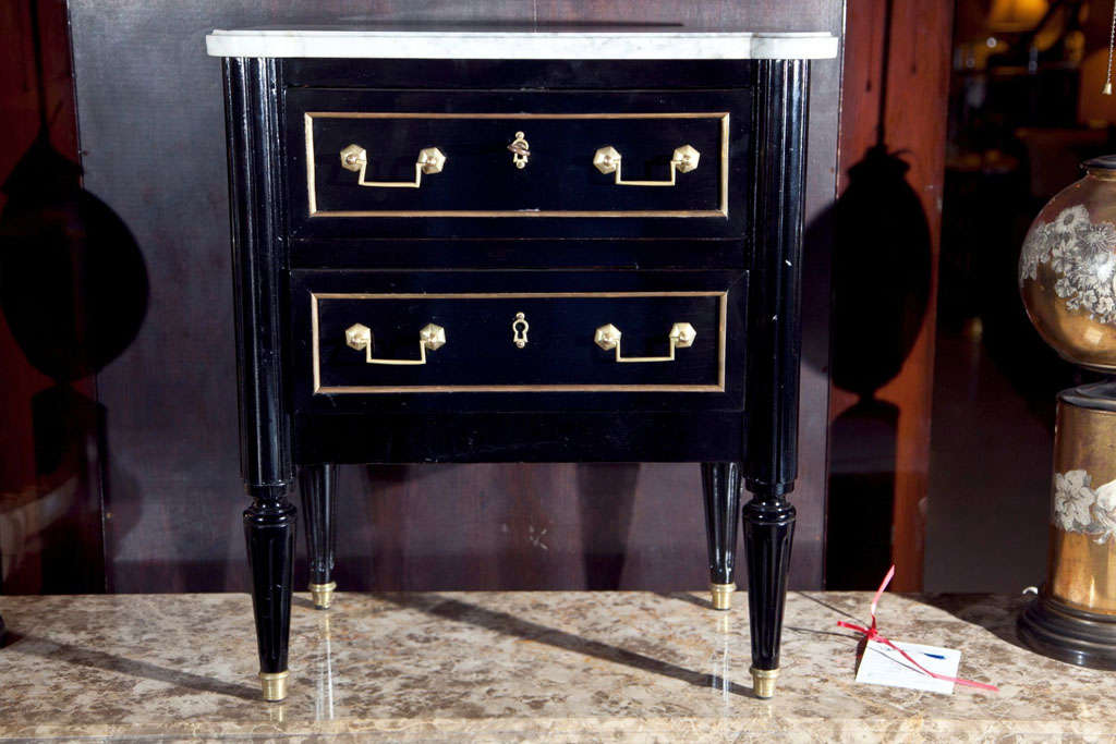A finely polished diminutive ebonized salesman sampler two-drawer commode. Handmade with oak secondaries. A fine example with brass drawer frames and brass pulls. White marble-top by Maison Jansen.