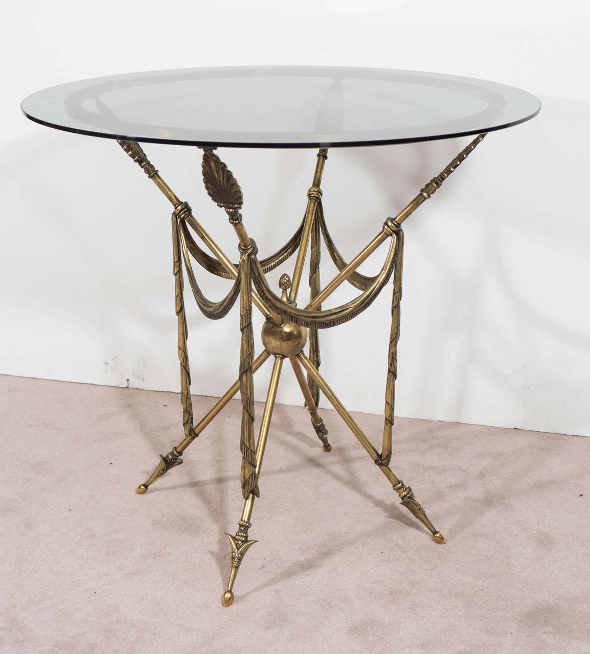 A vintage pair of French brass end or side tables, with arrow motif and neoclassical elements, circa 1950s. Smoked glass tops above a brass ring base, supported by four crossed legs, each stylized with anthemion vanes, terminating into decorative